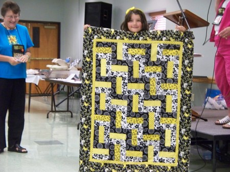 Mary Nell Magee teaches a Quilt Camp for children every summer. Morgan Radavich shows the quilt she made (2011). Morgan is now a teen-ager and member of the guild.