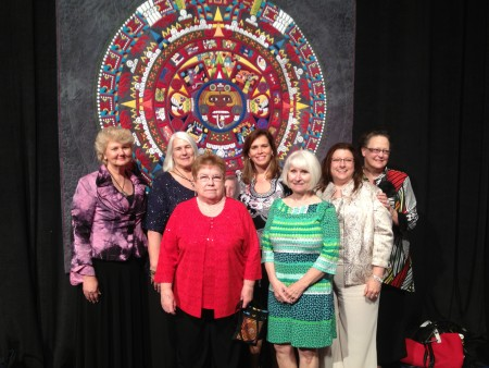 The Amazing Eight in Houston Front row: Mary Holman (Vicksburg, MS), Karen Fitzpatrick (Cleveland, OH), Wanda Myers (Shiner, TX) Back row: Carol Moellers (Greene, IA), Cindy Neville (St. Louis, MO), Mary Kay Runyan (Germantown, TN), Dana Lynch (Olive Branch, MS) Represented by picture on stick is Bridget Lilja (Chicago, IL)